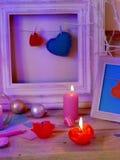 Composition intérieure de fête saisonnière des bougies allumées, décor, cadres en bois, lampes décoratives, coeurs de feutre, pap photo libre de droits