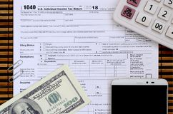 Composition of items lying on the 1040 tax form. Dollar bills, c. Alculator, smartphone, paper clip and notepad. The time to pay taxes Stock Photos