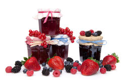 Composition with jars of red and black fruits jams and fresh fru Stock Photo