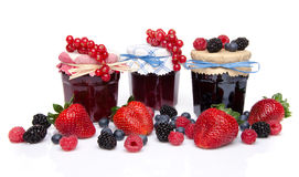 Composition with jars of red and black fruits jams and fresh fru Royalty Free Stock Images
