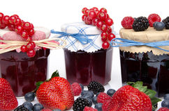 Composition with jars of red and black fruits jams and fresh fru Stock Images