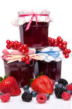 Composition with jars of red and black fruits jams and fresh fru Royalty Free Stock Photos