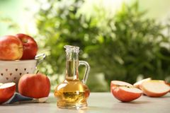 Composition with jug of apple vinegar on table. Space for text stock images