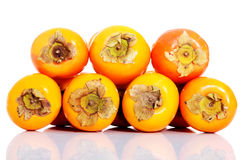 Composition of kaki fruits over white. Royalty Free Stock Photo
