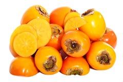 Composition of kaki fruits over white. Stock Image