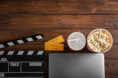 Composition with laptop, movie tickets and clapboard. On wooden background, top view Royalty Free Stock Photo