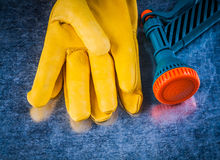 Composition of leather safety gloves and water sprayer agricultu Royalty Free Stock Images
