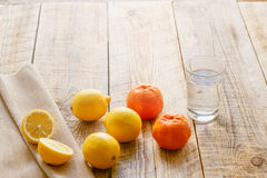 Composition of lemons, oranges and glass with water  wooden table Stock Image