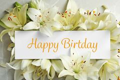 Composition of Lily flowers and card with greeting HAPPY BIRTHDAY. Top view stock photography