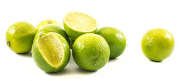 Composition of limes - whole and cut on a white background stock photo