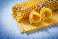 Composition of macaroni products on blue background food and dri Royalty Free Stock Photo