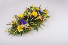 Composition made of artificial flowers, fruits, butterflies, birds and ears of wheat. Royalty Free Stock Images