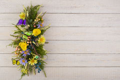 Composition made of artificial flowers, fruits, butterflies, birds and ears of wheat. Stock Photo