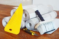 Composition with many rolls of wallpaper and tools for wallpapering Royalty Free Stock Images