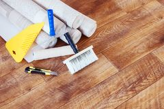 Composition with many rolls of wallpaper and various tools for home repair Stock Images