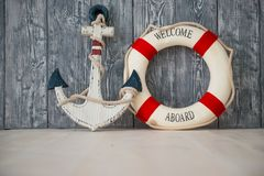 Composition on the marine theme with anchor and lifeline on wooden background.  Stock Photo