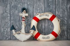 Composition on the marine theme with anchor and lifeline on wooden background.  Stock Photography