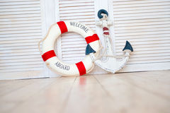 Composition on the marine theme with anchor and lifeline on wooden background.  Royalty Free Stock Images