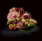 A composition of meat and vegetables with beer. A composition of meat and vegetables with a pot full of beer on a black textile Stock Image