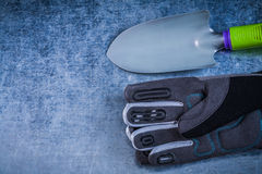 Composition of metal trowel protective gloves on scratched metal Stock Image