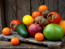 Composition of mix colored tropical and mediterranean fruits on wooden background. Concepts about decoration, Royalty Free Stock Photos