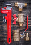 Composition of monkey wrench brass fittings water valve on woode Stock Image