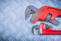 Composition of monkey wrenches on grooved metal background const Stock Photography