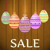 A composition of decorative, multicolored, Easter eggs on ribbons on the background of a tree texture. Sale to Easter. royalty free illustration