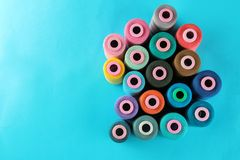 Composition with multi-colored thread spools on a bright blue background with a place for inscription stock photos