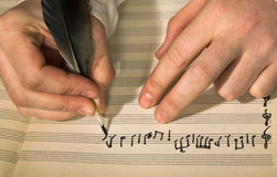 Composition of music. The hand writes musical notes a feather Stock Photography