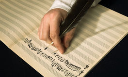 Composition of music. The hand writes musical notes a feather Stock Photos