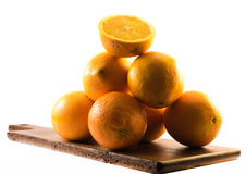 Composition of nicely colored oranges on a white background - front and back and cut in half on a wooden board.  Royalty Free Stock Images