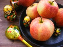 Composition Of Red And Yellow Apples On Black Cast Iron Plate With Traditional Russian Nesting Dolls Matrioshka And Painted Spoon Royalty Free Stock Photo