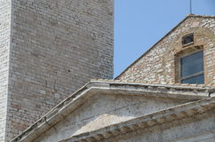 The composition of old buildings roofs in Assisi. Sandstone in full sun. Tympanon and pitched roof Royalty Free Stock Photo
