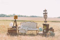 The composition of the old-fashioned sofa with the knitted plaid, wooden plaques with the signs ``Wedding, dancing. ``, vintage suitcases with globe and flowers Stock Images