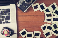 Composition of old photo camera, laptop and photo slides Royalty Free Stock Images