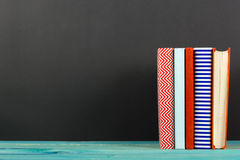 Composition with old vintage colorful hardback books, diary on wooden background Stock Photography