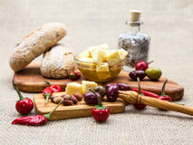 Composition with olive wood, olives, bread, cheese pieces in olive oil, spices Stock Image