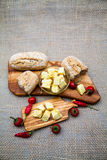 Composition with olive wood, olives, bread, cheese pieces in olive oil, spices Royalty Free Stock Images