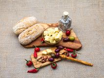 Composition with olive wood, olives, cheese pieces in olive oil, bread and spices Stock Photography