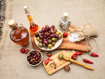 Composition with olive wood, olives, cheese pieces in olive oil, spices Stock Photo