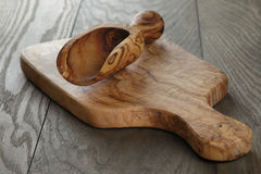Composition with olive wood scoop on top of oak table Stock Photos
