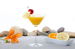 Composition with a orange cocktail, sand and pebble stones Stock Images