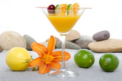 Composition with a orange cocktail, sand and pebble stones Stock Photo