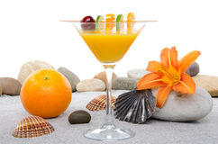 Composition with a orange cocktail, sand and pebble stones Royalty Free Stock Photos