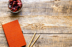 Composition of orange notebook with flower sachets on wooden tab Stock Image
