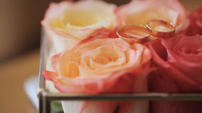 Composition of orange roses stands on table with bridal rings on it. Bouquet of flowers is prepared for wedding ceremony for bride to keep it in her hands and stock footage