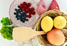 A wooden spoon, lemons, oranges and raspberries. royalty free stock photography