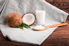 A composition of organic and bright brown coconuts,  wooden spoon with grated nuts and  coconut milk on a dark brown wooden table. A transparent glass of Royalty Free Stock Photos