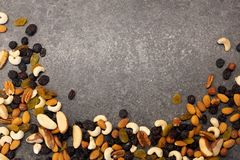 Composition with organic mixed nuts on dark background, top view. Space for text. stock photography